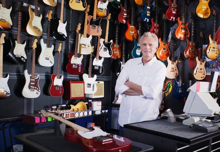 Older man behind cash register at guitar store
