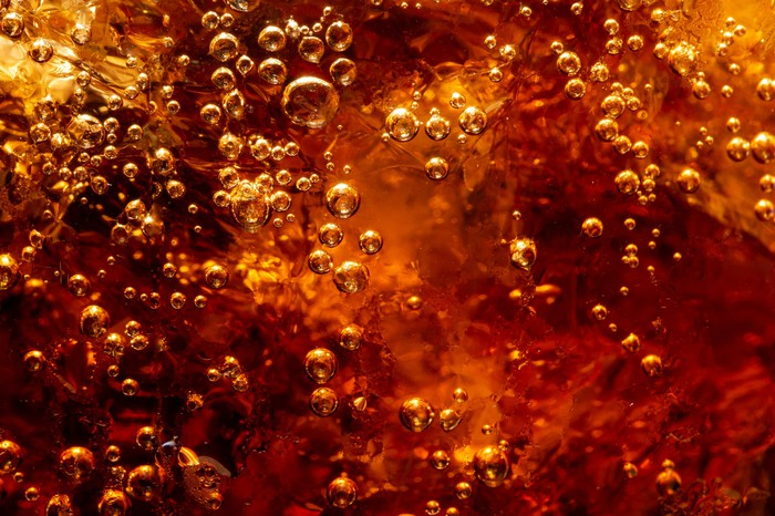 Closeup of dark carbonated soft drink with ice.
