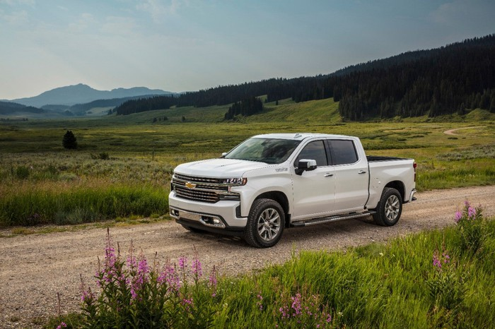 A white Chevy Silverado driving on a dirt road, with a green field in the background