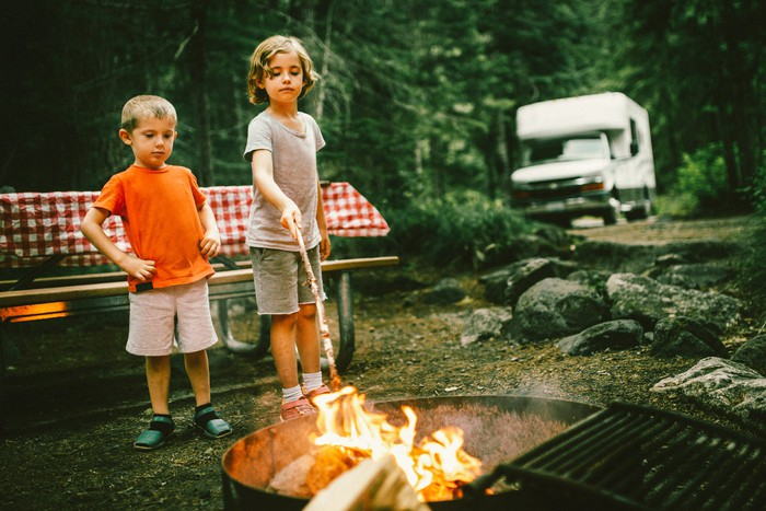 Two kids at a campfire, with an RV in the background.