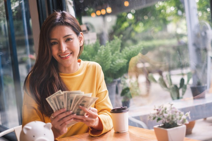 A happy young woman is sitting at a cafe with hundred dollar bills in her hand.