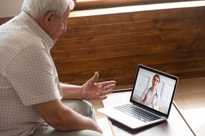 A man conferring with a doctor over a laptop.