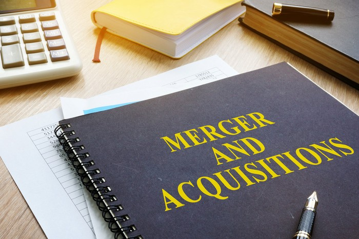 """A spiral bound book titled """"Merger and Acquisitions"""" amid other books and a calculator on a desk."""