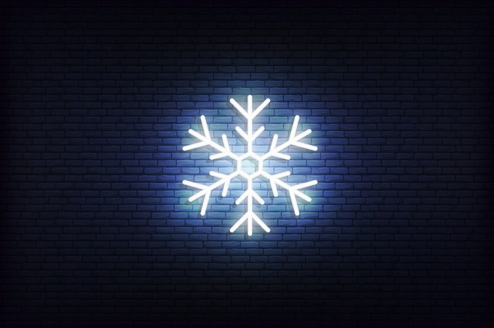 A snowflake illuminated against  a black background.