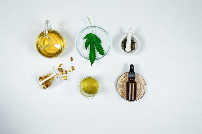 cbd, thc oil, capsules, and marijuana leaf on a table