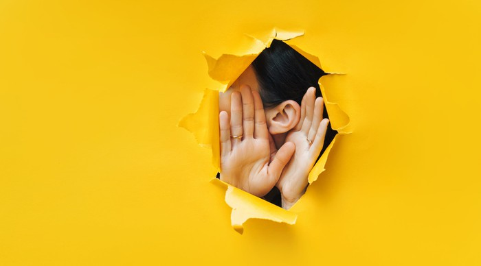 A person trying to hear through a ripped yellow paper wall.