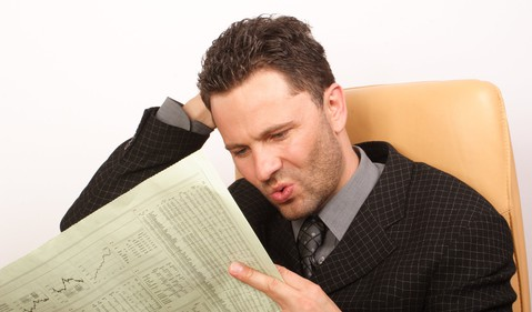 Curious Man Reading Financial Newspaper Getty
