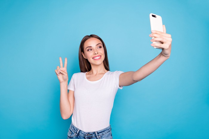 Woman giving peace sign while taking selfie