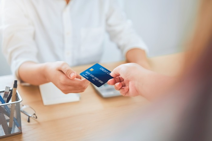 Person handing credit card over to another person.