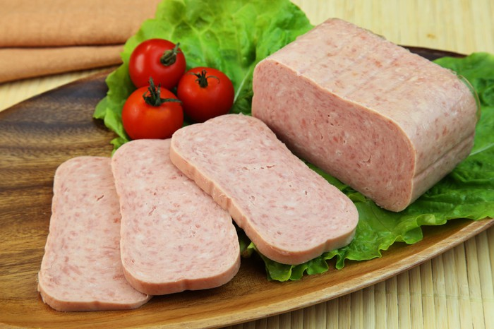 Processed ham similar to spam, sliced on a wooden cutting board with cherry tomatoes and lettuce.
