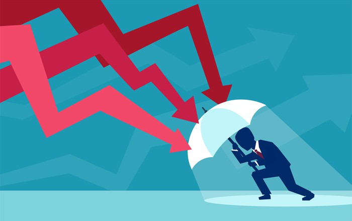 Vector of a businessman with umbrella defending himself from the falling red arrows of a stock market crash