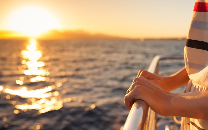 A pair of hands holds a railing on a cruise ship as the sun sets behind it.