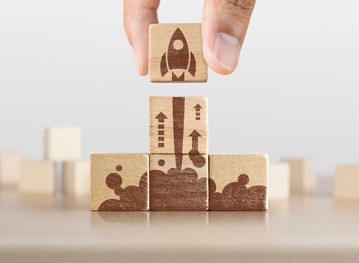 Wooden blocks forming a picture of a rocket taking off