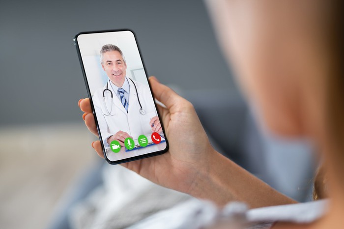 Person holding a smartphone displaying a video call with a doctor.