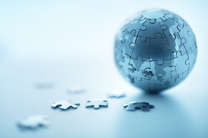 Jigsaw puzzle pieces next to a small globe formed by jigsaw puzzle pieces