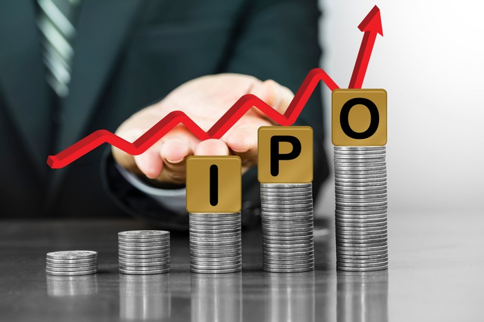 Five increasingly higher stacks of coins with blocks spelling out IPO on the three highest stacks and a businessman holding a red line trending up in the background