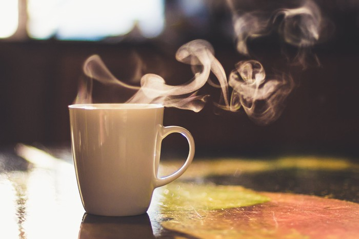 A steaming cup of coffee in a white cup sits on a wooden table against a dimly lit background.