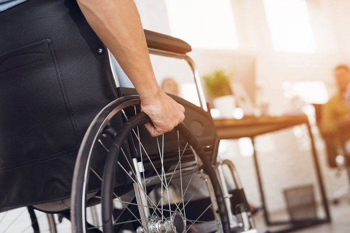A person pushing the wheel of their wheelchair.