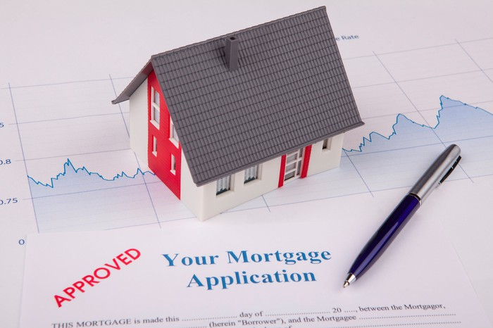 """A model home resting on top of a paper chart and a document that says """"Your mortgage application: APPROVED."""""""