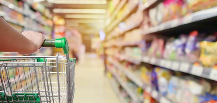 A shopper pushes a shopping cart through a supermarket aisle.