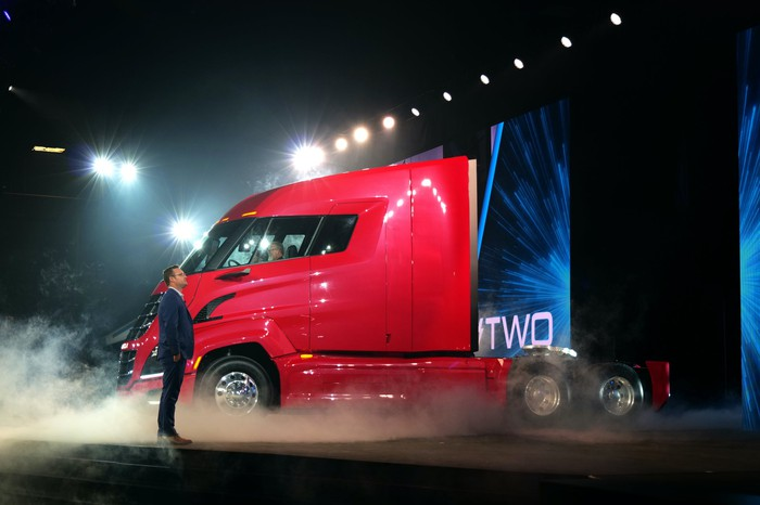 Milton is shown standing on an auto-show stage with a red Nikola Two, an electric semi truck.