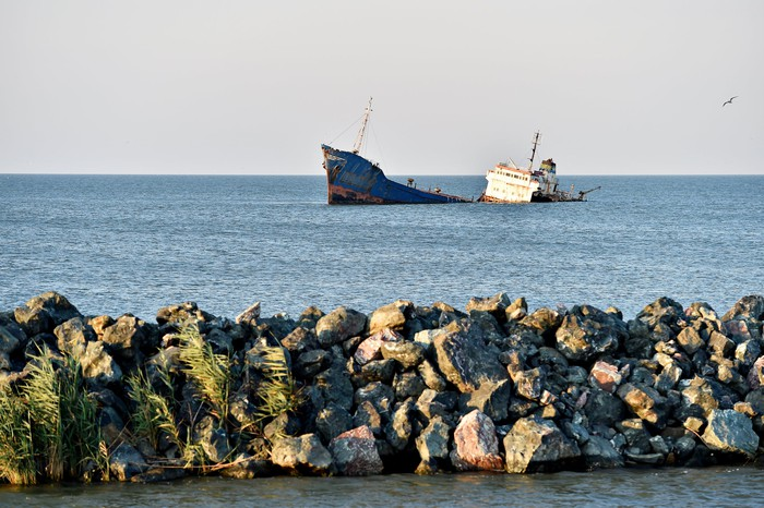 A large modern shipwreck in a sunlit sea with a rocky breakwater in the foreground.