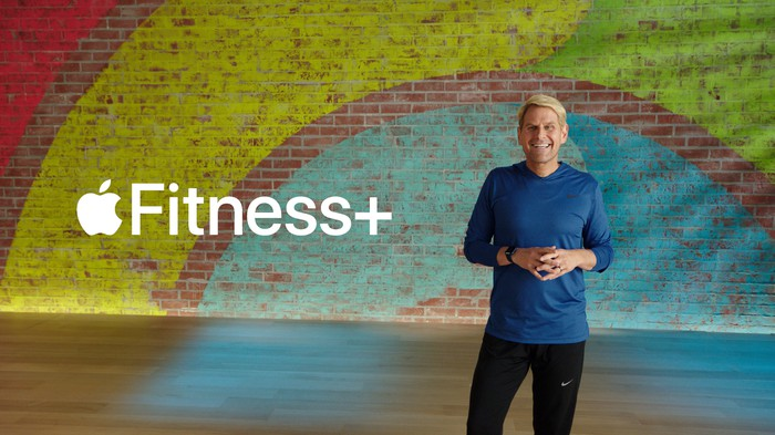 Apple Fitness+ leader standing in front of as rainbow wall