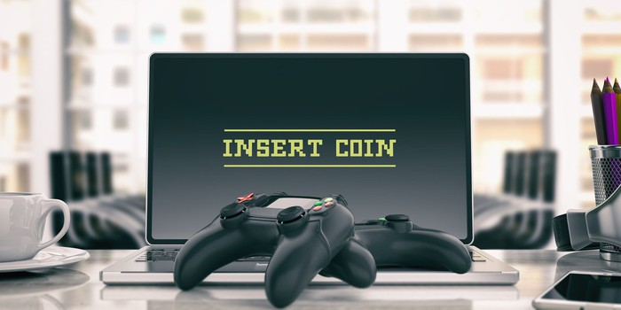 Two game controllers and a laptop with text 'Insert Coin.'