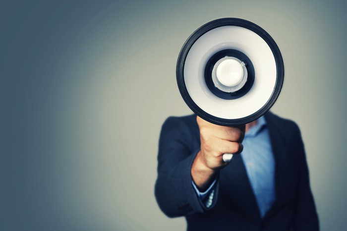 A man in a suit speaks through a megaphone.