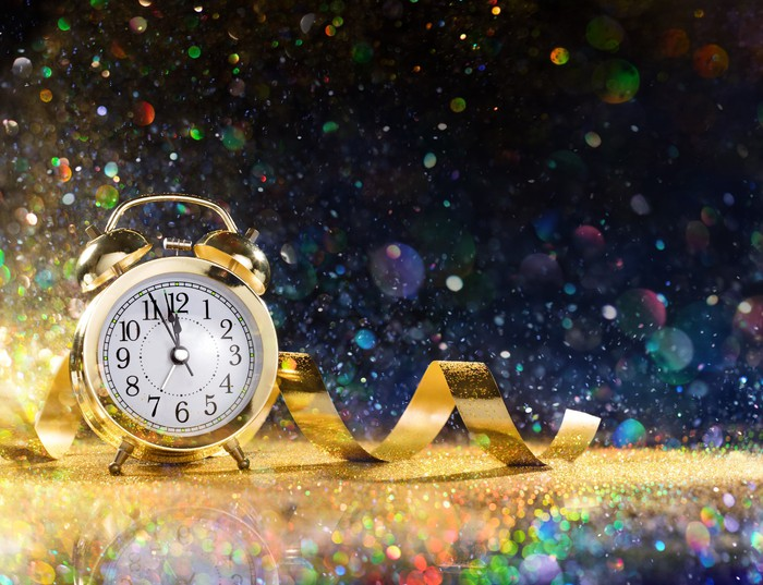 A golden clock surrounded by confetti.