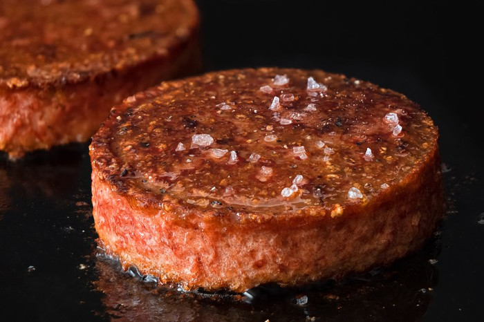 A plant-based burger sizzles on an hot oven top.