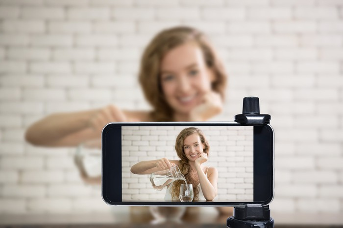A woman vlogger streaming using a video sharing service.
