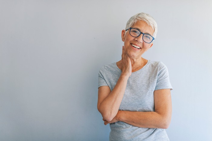Smiling older woman standing against gray wall