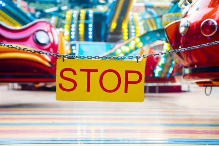 "A chain with the word ""stop"" surrounding empty amusement park rides."