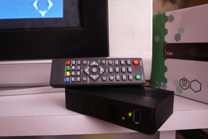 a cable remote and cable box on a TV stand next to a TV.