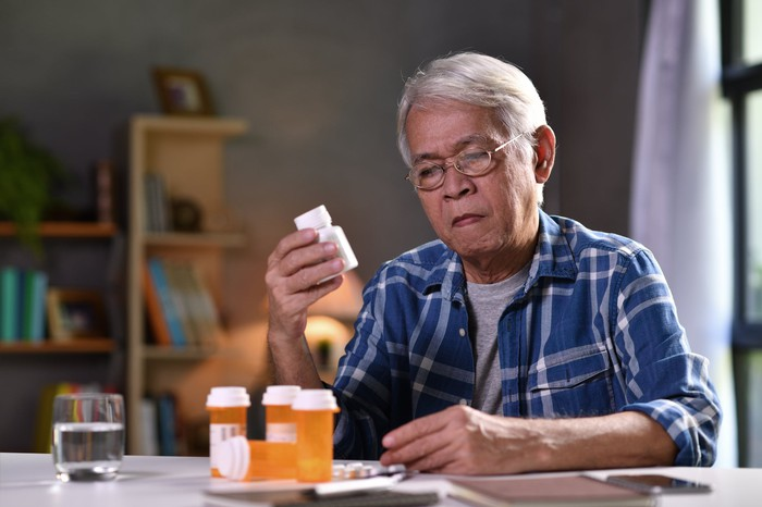 Elderly person at a table with bottles of pills.