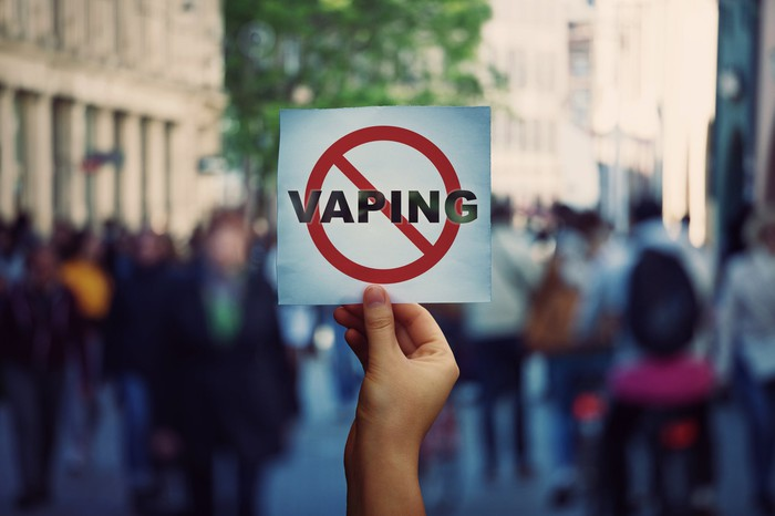 Human hand holding a protest banner with stop vaping message