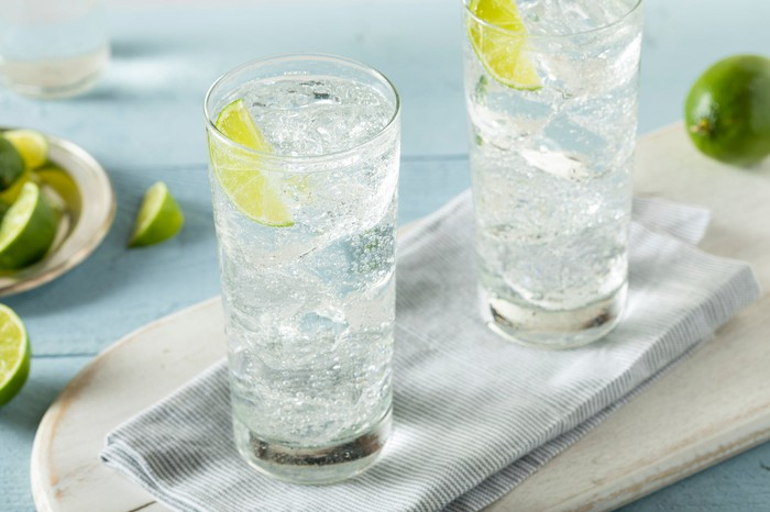 Two glasses of hard seltzer with ice cubes and slices of lime.