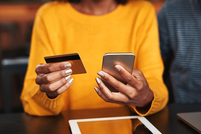 A woman in a yellow sweater with a credit card in one hand and a smartphone in the other.