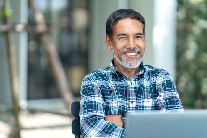 Smiling man at laptop outdoors