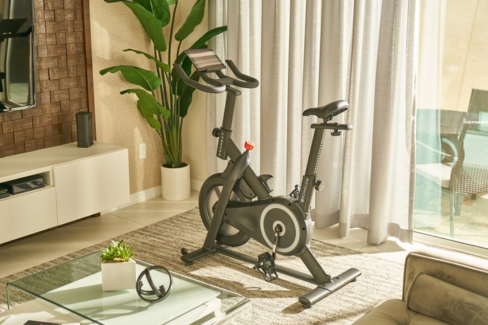 The Prime Bike in a furnished room with a sliding glass door and curtains behind it