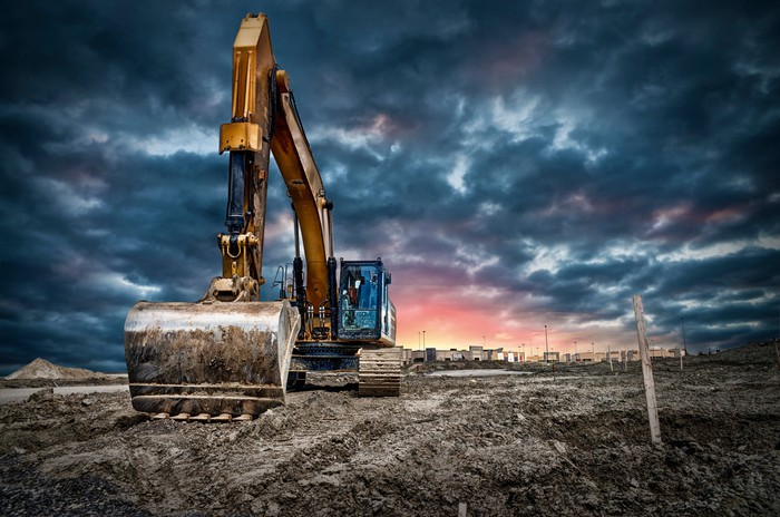 Construction machinery at work against a dramatic sky.