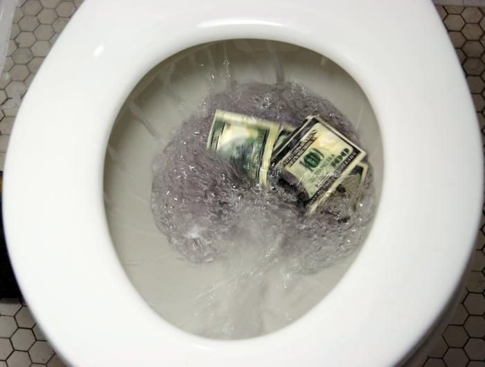 Flushing $100 bills down the toilet.