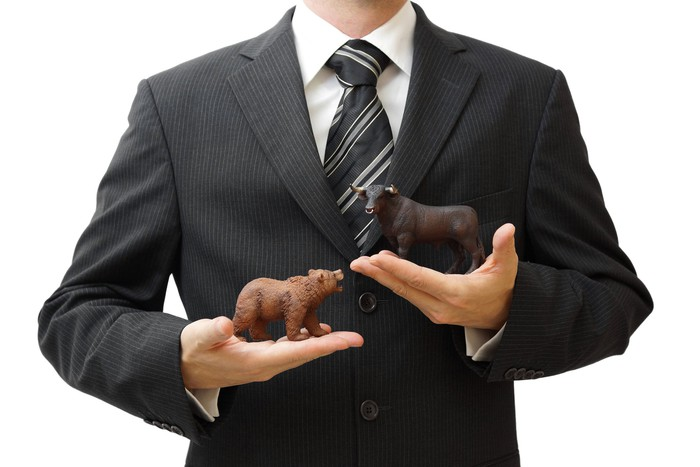 Businessman holding a tiny bear and a tiny bull figurine.