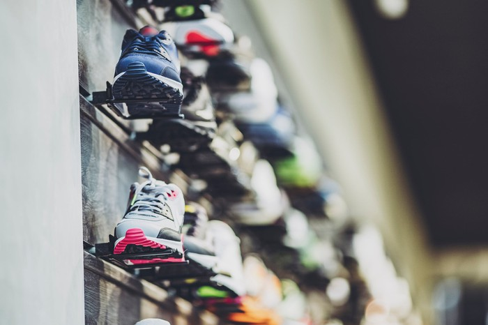 Multicolored sports shoes or running shoes on a store wall display.
