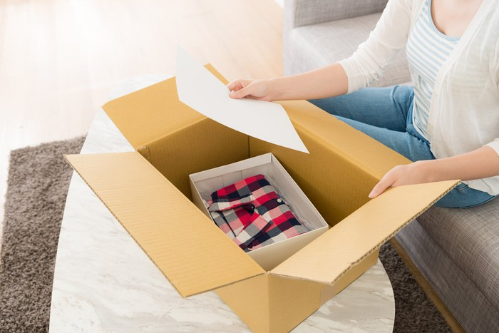 A woman opening a box with a shirt in it and looking at a piece of paper