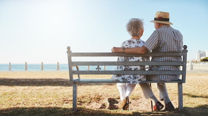 Older couple sitting on bench looking out at beach.