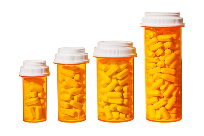 Four pill bottles stand side by side, with each bottle slightly larger than the previous one.