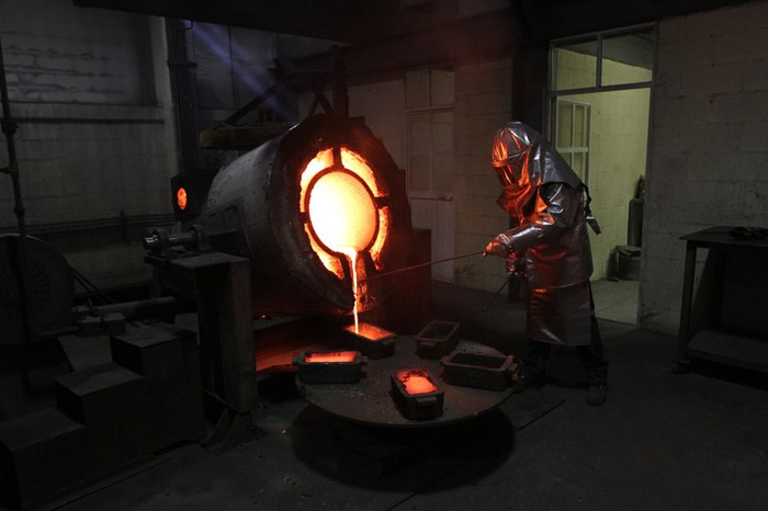 worker pouring molten silver out of a ladle