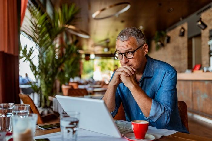 Man sitting behind a laptop looking worried